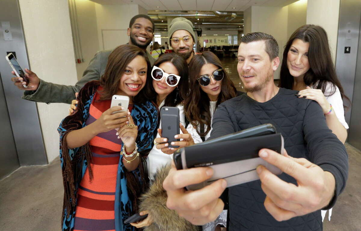 Dutch Small, second from right, takes a selfie with Amber Elliott, front left, Houston Chronicle society writer, and bloggers Saba Jawda, Sarah Jawda, Magen Pastor, front right, Dominique McGee, back left, and Josh Robertson, back center, after a brief runway style fashion show at the Houston Chronicle Monday, Dec. 12, 2016 as a preview for Houston's Day For Night festival.