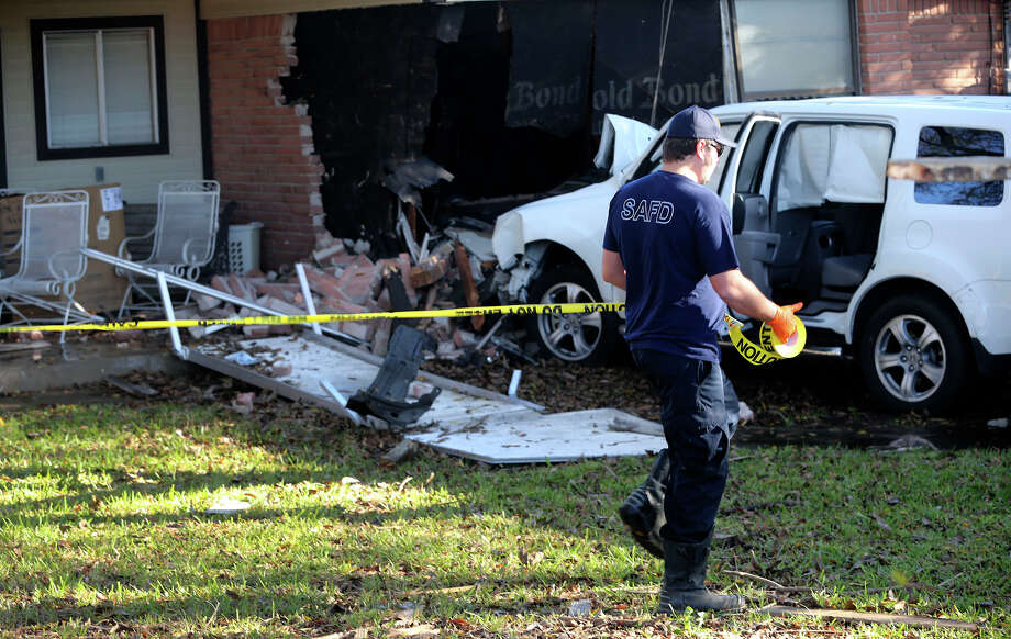 A San Antonio firefighter marks off a house Monday December 12, 2016 on the 200 block of Tammy Drive after a stolen SUV smashed through a fence and crashed into the back of the house. Roger Barajas, who works at nearby SWBC, said he noticed the car in the man's back yard and approached the man and asked if he was hurt and Barajas called 911. San Antonio battalion chief Patrick Zepeda said the vehicle ran through the back of a church parking lot and into the back of the man's house taking out two load bearing walls. The man was removed by EMS and was being checked in an ambulance. The driver of the vehicle fled the scene. Photo: John Davenport, San Antonio Express-News / ©San Antonio Express-News/John Davenport