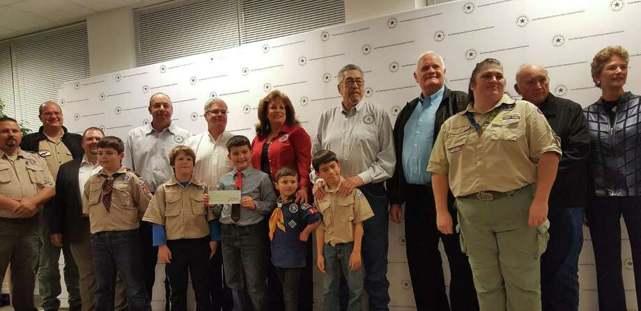 Cub Scout Pack 911 from Porter poses with the East Montgomery County Improvement District board after receiving a micro grant for $1,882.73 from to purchase a canopy, tables and turkey fryer kit during the regular board meeting at the EMCID Complex in New Caney Dec. 8. Photo: Melanie Feuk
