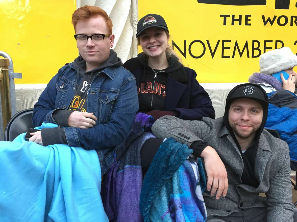 Reid Cammack, Sara Woolf and Zach Dunnington, who have been camped out overnight, wait for Hamilton tickets to go on sale, outside the OrpheumTheatre, in San Francisco, California, on Monday, Dec. 12, 2016.