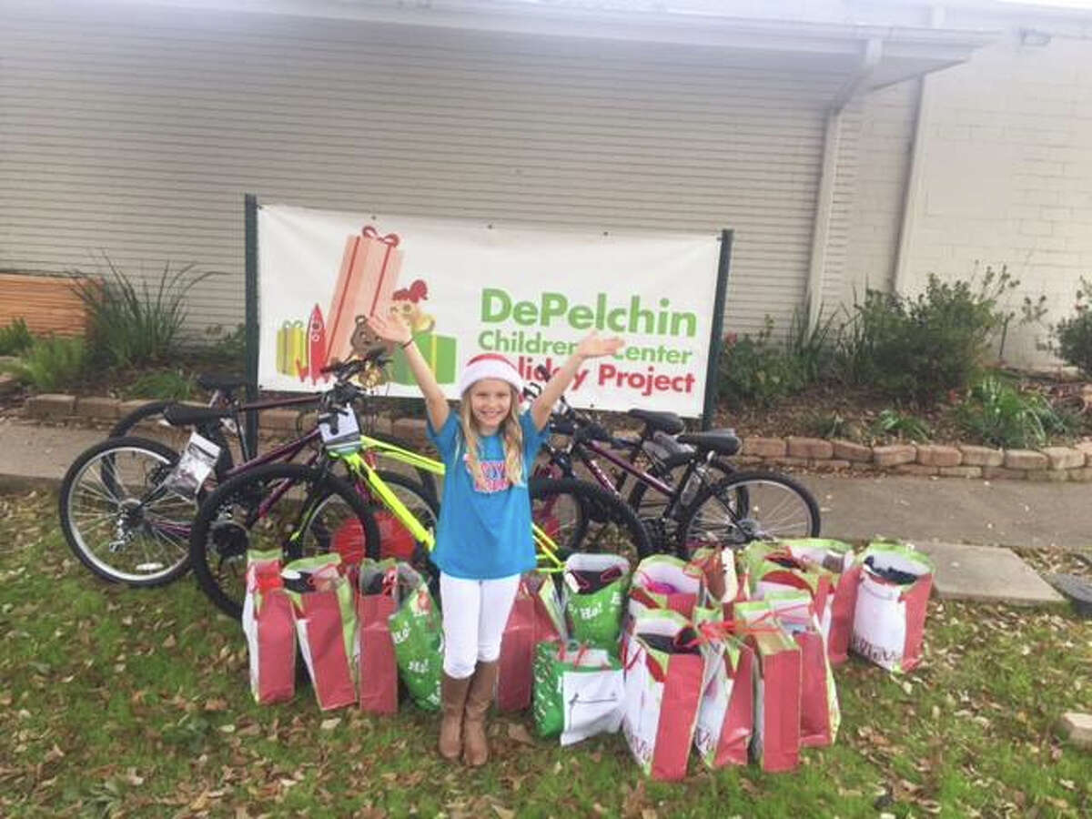 Kirstyn Jackson, 11, poses with bikes and presents on some foster care students' wish lists in 2015.