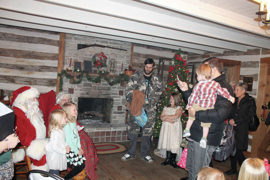 Youngsters pose with Santa and Mrs. Claus on Sunday at the Yanda Log Cabin in downtown Edwardsville. The meet-and-greet with the couple from the North Pole included live music, a canned-good donation and cookies and refreshments for visitors, all in the historic ambiance of the village's oldest structure. The event is presented each year by the Glen Carbon Historical and Museum Commission and the Glen Carbon Kiwanis Club. Photo: Bill Tucker • Intelligencer