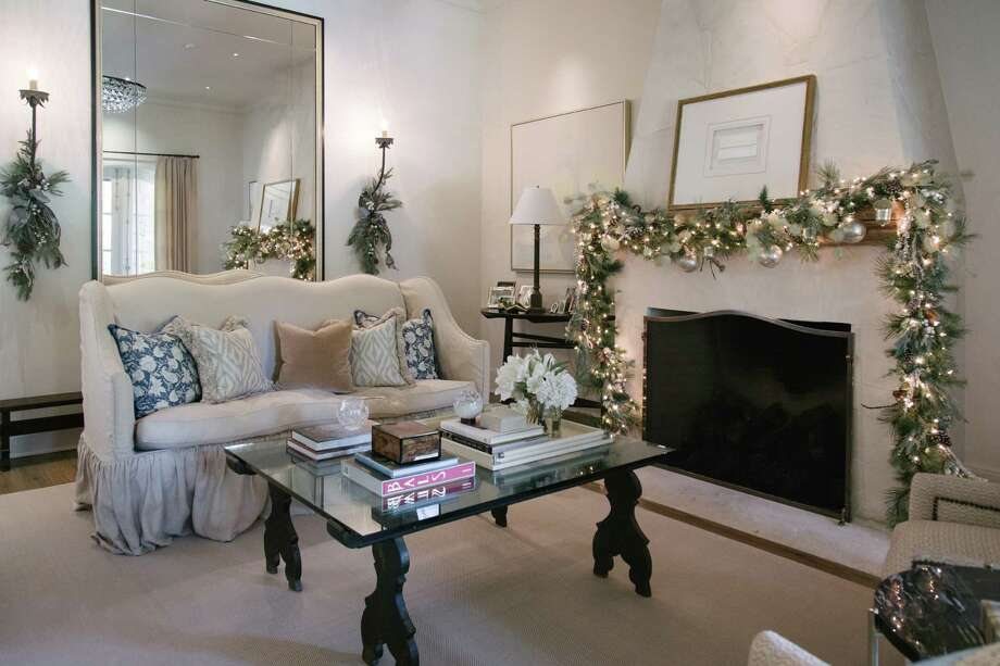 Evergreen garland on the fireplace mantle and sprigs dangling from wall sconces add instant holiday warmth to the Memorial home of Rockets head coach Mike D'Antoni and his wife, Laurel. Photo: Courtesy Of Marie Flanigan Interiors
