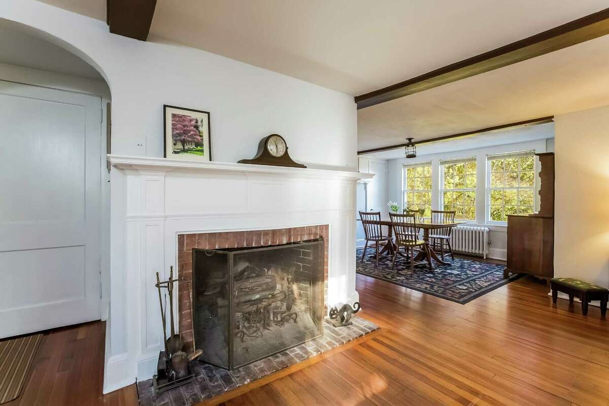 The living room is open to the dining room and has a fireplace and an arched doorway to the stairs to the second floor.