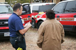 Conroe resident Corona Lourdes speaks with an investigator after the building where she lives caught fire on Monday, Dec. 12, 2016, in the 600 block of East Davis Street.