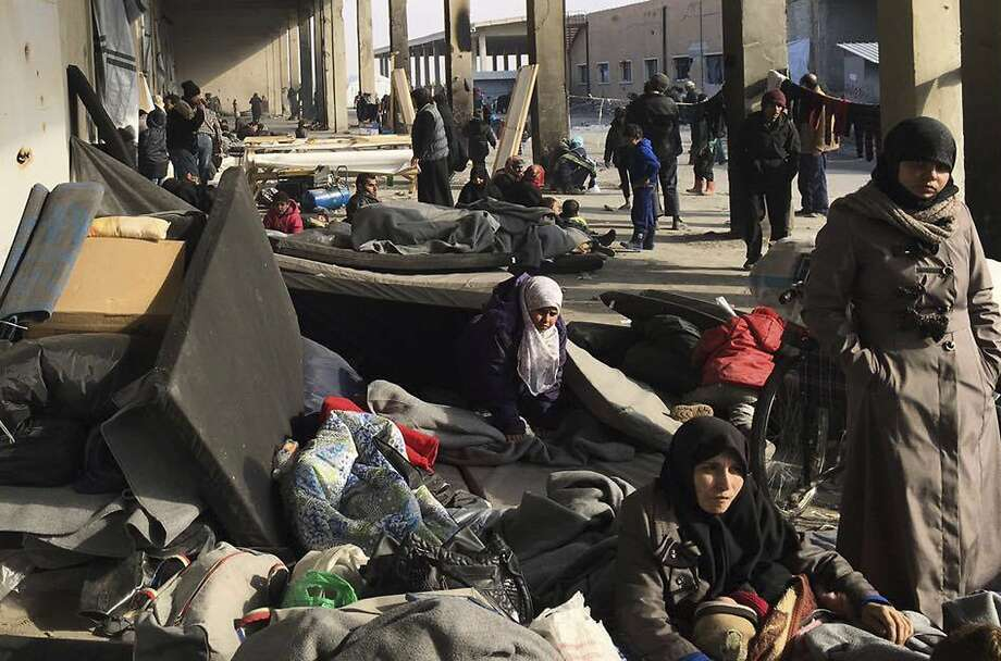Syrians who were displaced with their families from eastern Aleppo gather at a refugee shelter in the village of Jibreen south of the besieged city. Photo: Uncredited, Associated Press