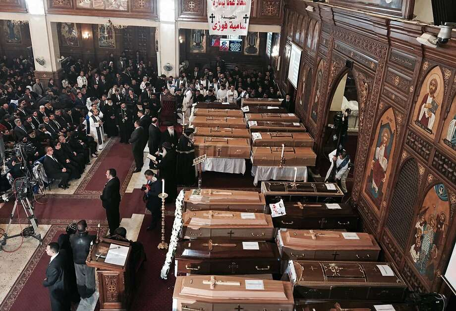 The coffins of the 25 victims of a huge bombing at St. Mark's Cathedral in Cairo Sunday are laid in front of the altar at the Virgin Mary Church, where they were eulogized at a mass funeral. Photo: Nariman El-Mofty, Associated Press