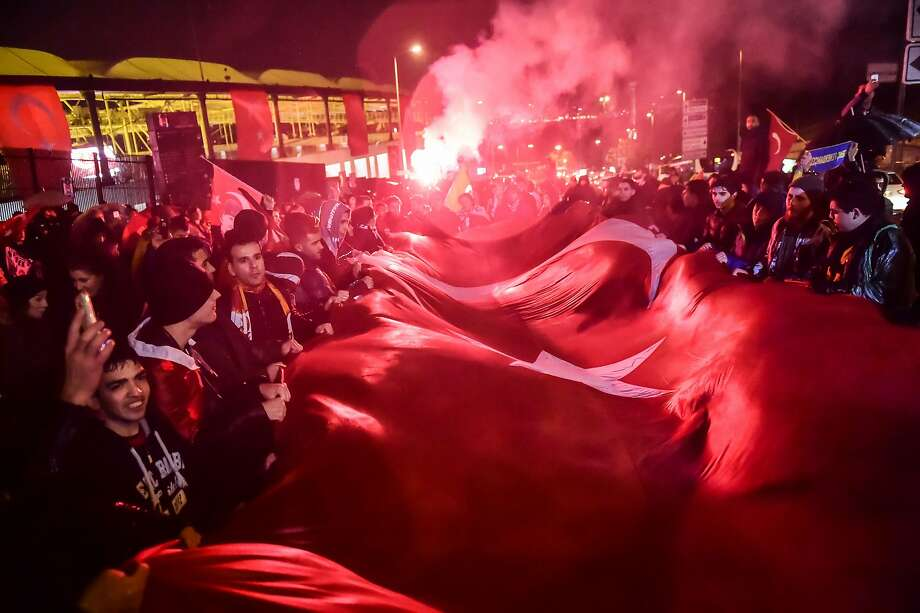 Turkish soccer fans hold a giant national flag during a rally near the stadium where two bombs killed 44 people on Saturday. The attacks were claimed by a radical Kurdish separatist group. Photo: YASIN AKGUL, AFP/Getty Images