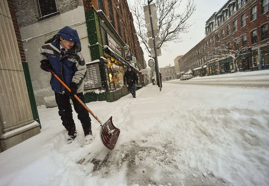 Theron Wilkinson, 13, shovels the sidewalk in front of his parent's business on Main Street in Brattleboro, Vt., during a snowstorm. Two fatal car crashes were blamed on the weather. Photo: Kristopher Radder, Associated Press