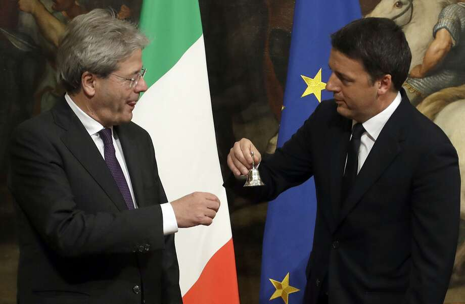 Italian outgoing Premier Matteo Renzi, right, hands over the cabinet minister bell to new Premier Paolo Gentiloni during the handover ceremony at Chigi Palace Premier's office, in Rome, Monday, Dec. 12, 2016. Paolo Gentiloni, a Democrat serving as foreign minister, formed Italy's new government Monday, keeping several key ministers from the coalition of Matteo Renzi, who resigned last week. (AP Photo/Gregorio Borgia) Photo: Gregorio Borgia, Associated Press
