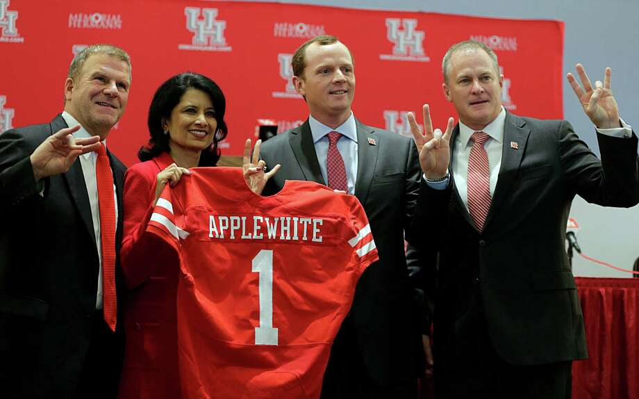 University of Houston Board of Regent Chairman Tillman Fertitta left, President Renu Khator  2nd from left, Major Applewhite 2nd from right, and Vice President of Athletics Hunter Yurachek  pose for photographs during a press conference announcing Applewhite as the next University of Houston football head coach at TDECU Stadium Dec. 12, 2016, in Houston. Photo: James Nielsen, Houston Chronicle / © 2016  Houston Chronicle