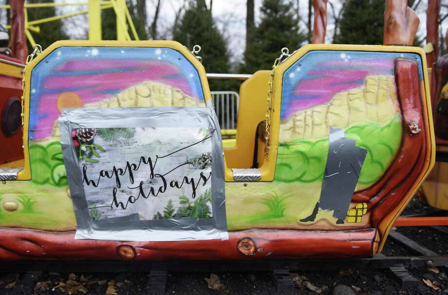 """Duct tape covers up the caricature of a black African man trying to cook a white hunter on the side of a children's ride at the annual Reindeer Festival at Sam Bridge Nursery in Greenwich, Conn. Monday, Dec. 12, 2016. The controversial scene on the side of the kiddie train ride was reported over the weekend and is now covered up with duct tape and """"Happy Holidays"""" signs. Photo: Tyler Sizemore / Hearst Connecticut Media / Greenwich Time"""