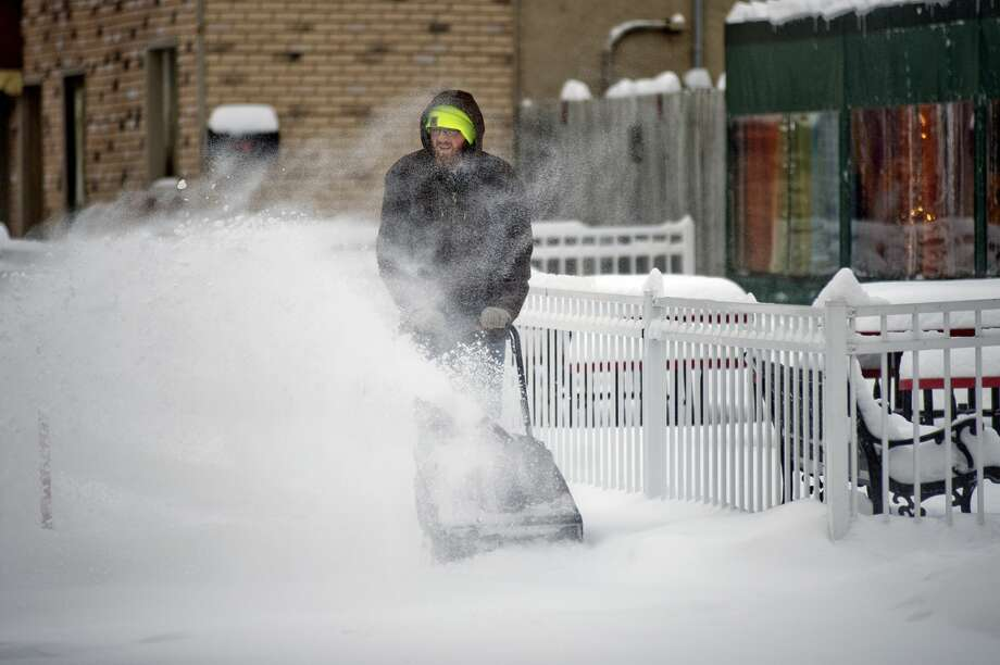 Kameron Sergent uses a snowblower to clear snow off the sidewalk at the intersection of Main and Townsend street on Dec. 12, 2016 in downtown Midland. Photo: NICK KING | Nking@mdn.net/Nick King