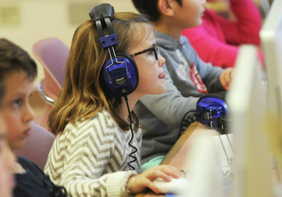 """Third-grader Gigi McKenzie concentrates while working on a coding project during the """"Hour of Code"""" program at Cos Cob School in the Cos Cob section of Greenwich, Conn. Monday, Dec. 12, 2016. Facilitated by the Bruce Museum, the coding workshop teaches the basics of coding and computer science to first- through third-graders at Cos Cob School throughout the week. During the month of December, the Bruce Museum will bring """"Hour of Code"""" to Glenville School, Julian Curtiss School, Eastern Middle School, North Street School, Cos Cob School, Parkway School and the Cos Cob Library, as well as John F. Kennedy Magent School and Park Avenue School in Port Chester, N.Y. Photo: Tyler Sizemore / Hearst Connecticut Media / Greenwich Time"""