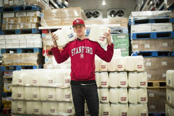 Isaac Gonzalez, a Costco temporary worker stocks milk at Costco on Monday, Dec. 12, 2016 in San Francisco, Calif.