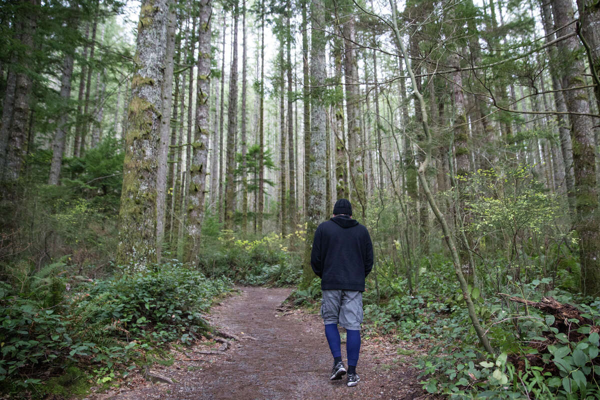 Keith Johnson walks on the trail to Rattle Snake Ledge in North Bend, Dec. 3, 2016. Johnson's path inward began around puberty; he began feeling out of place in middle and high school. After the end of a 14-year relationship, Keith says he was depressed and in a trance.