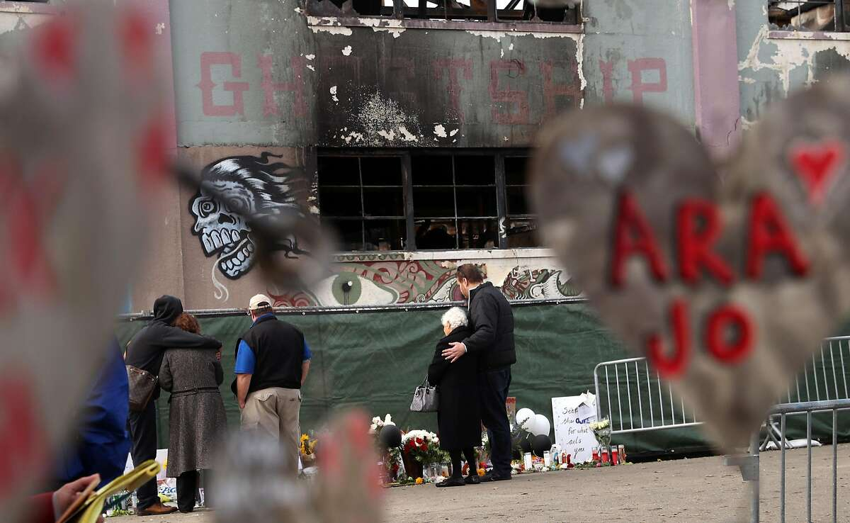 Family members of a Ghost Ship warehouse fire victim embrace at the scene on 31st Avenue in Oakland, Calif., on Monday, December 12, 2016.