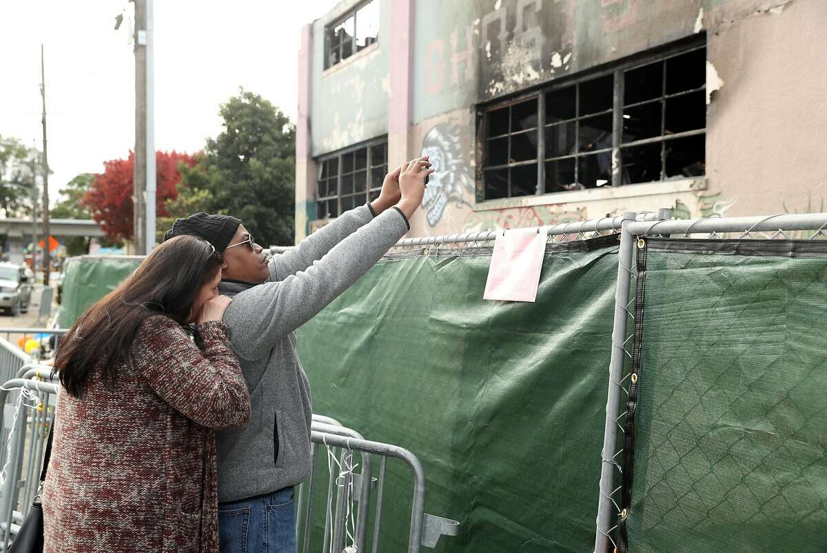 Jamel Daniels and his wife, Karen Talton, of Oakland visit the Ghost Ship warehouse, the scene of a fire that claimed 36 lives, in Oakland, Calif., on Monday, December 12, 2016.