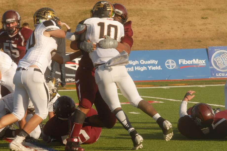 Abernathy defensive end Xavier Rivera, shown wrapping up Post running back A.J. Reed, 10, for a loss in a playoff game this year, was voted honorable mention on the Class 2A All-State Football Team. Photo: Skip Leon/Plainview Herald