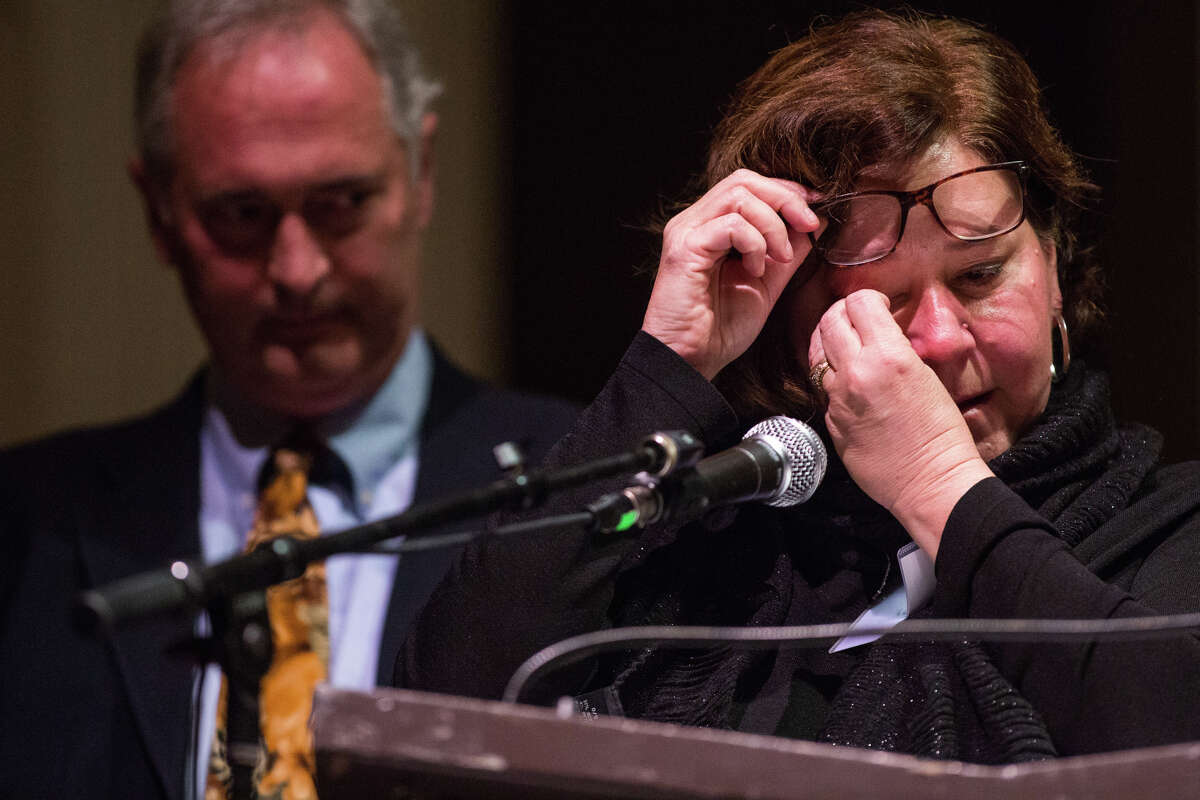 Laura Crooks wipes tears from her eyes as she and her husband, Todd, speak at the King County Behavioral Health Legislative Forum about their son, Chad, who lost his life to suicide earlier this year, at Town Hall in Seattle on Dec. 7, 2016.