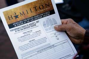 A man looks over the guidelines for buying Hamilton tickets as he waits in line for tickets to go onsale, in San Francisco, California, on Monday, Dec. 12, 2016.
