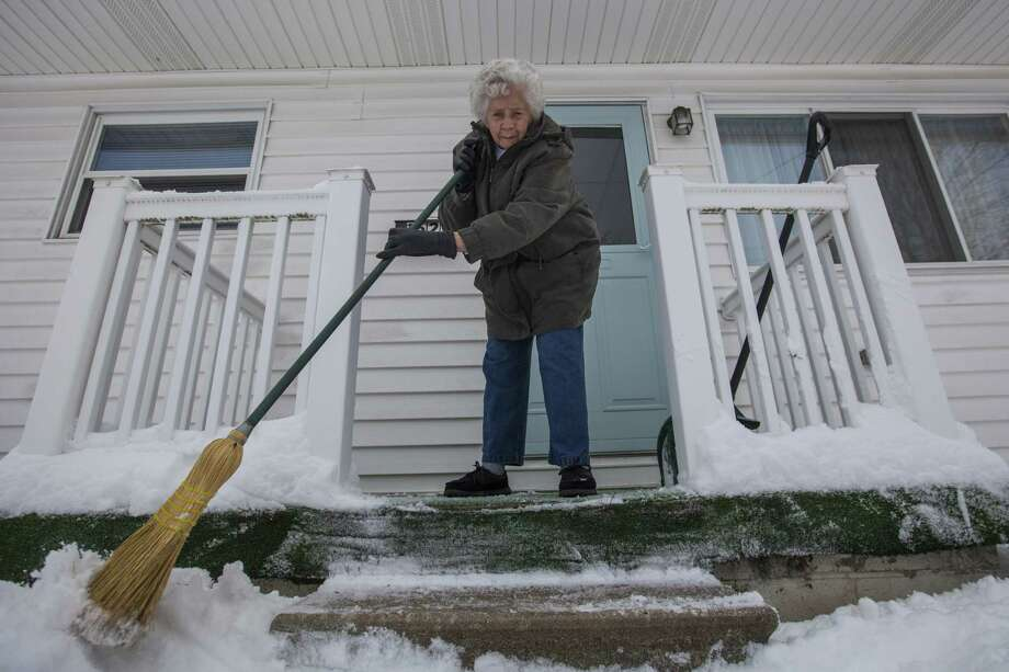 Irene Dudek of Saginaw, Mich., sweeps off her front porch Monday after the city received nearly 9 inches of snow overnight, according to the National Weather Service. Hundreds of Michigan schools remained closed as the state dug out. Photo: Josie Norris, MBO / The Saginaw News/MLive.com
