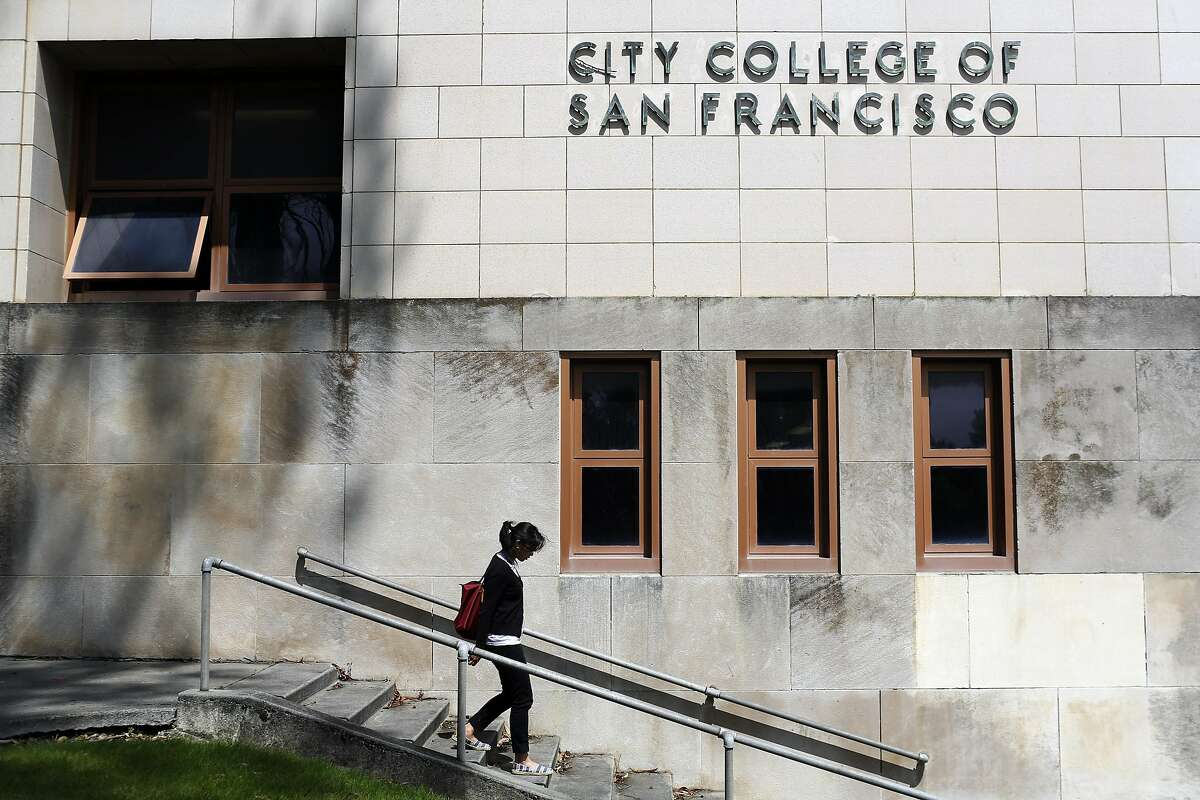 Claudeen Narnac walks down the steps in front of a City College of San Francisco sign in San Francisco on July 3, 2013.