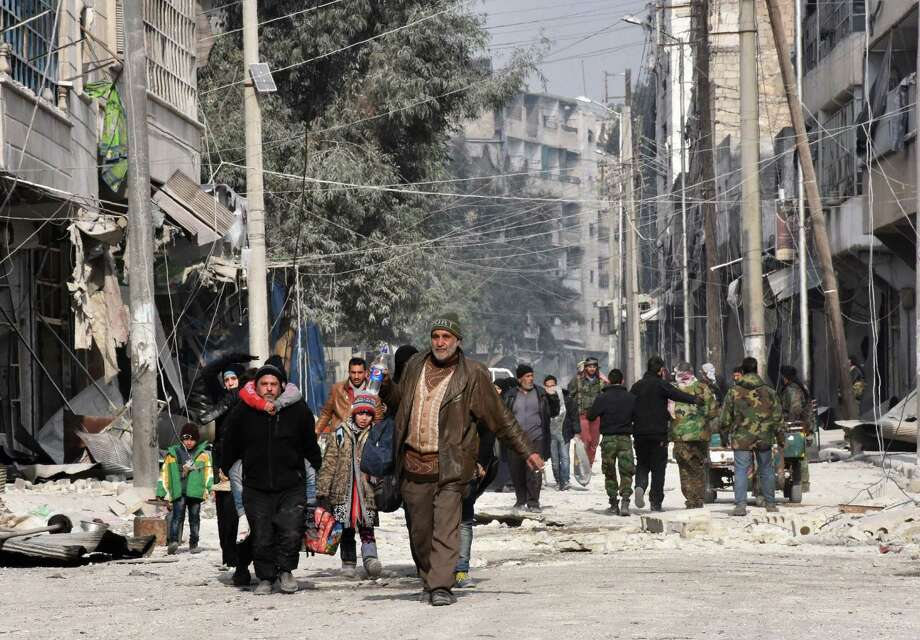 Syrian residents flee violence in Aleppo's eastern al-Salihin neighborhood on Monday after regime troops retook the area from rebel fighters. Photo: GEORGE OURFALIAN, Stringer / AFP or licensors
