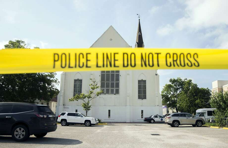 FILE - In this June 19, 2015 file photo, police tape surrounds the parking lot behind the AME Emanuel Church as FBI forensic experts work the crime scene, in Charleston, S.C. Prosecutors who wanted to show that Dylann Roof was a cruel, angry racist simply used his own words at his death penalty trial on charges he killed nine black people in June 2015 at a Charleston church. Roof's two-hour videotaped confession less than a day after the shooting and a handwritten journal found in his car when he was arrested were introduced into evidence Friday, Dec. 9, 2016. (AP Photo/Stephen B. Morton, File) Photo: Stephen B. Morton, Associated Press