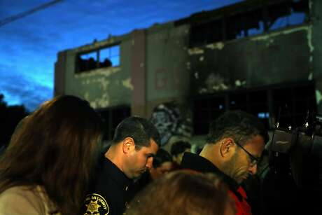 Attendees observe a moment of silence during a memorial service for the Ghost Ship warehouse fire victims in front of the structure on 31st Avenue in Oakland, Calif., on Monday, December 12, 2016.