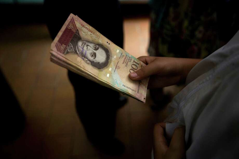 "A customer holds a stack of 100-bolivar notes  at a bakery in downtown Caracas, Venezuela, Monday, Dec. 12, 2016. Venezuelans are rushing to spend their 100-bolivar notes after a surprise announcement that they will be taken out of circulation this week. President Nicolas Maduro said on Sunday that his government would be pulling the bills to stop the ""mafias"" who smuggle contraband on the Colombian border. (AP/Photo/Fernando Llano) Photo: Fernando Llano, STF / Copyright 2016 The Associated Press. All rights reserved."