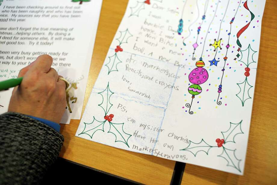 GE administrative assistant, Darlene Muscanell, writes back to a child who sent a letter to Santa on Monday, Dec. 12, 2016, in Schenectady, N.Y.  For the last 22 years GE employees have been volunteering their time to answer letters written to Santa from children.  The employees use form letters that they then add to to personalize for each child.   (Paul Buckowski / Times Union) Photo: PAUL BUCKOWSKI / 20039113A