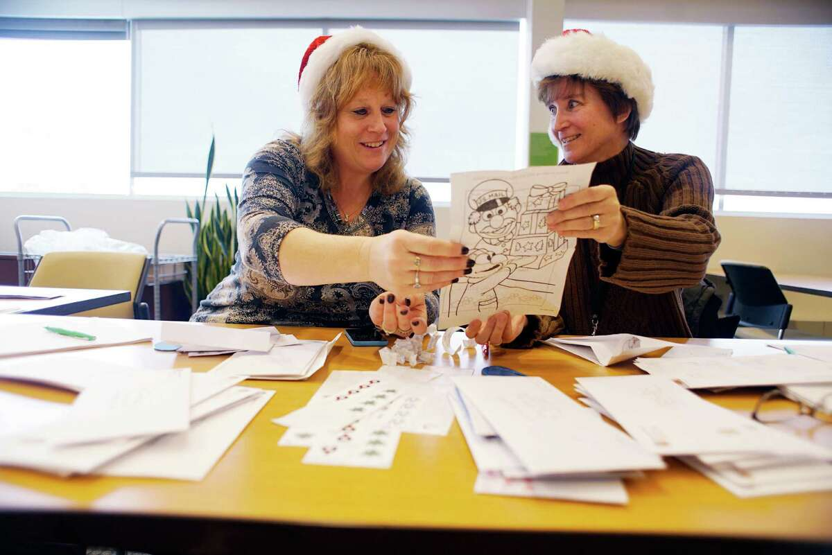 Joanne Vinciguerra, left, a GE administrative assistant and Kim Janeczko, a GE contract manager, look over a letter written to Santa from a child on Monday, Dec. 12, 2016, in Schenectady, N.Y. For the last 22 years GE employees have been volunteering their time to answer letters written to Santa from children. (Paul Buckowski / Times Union)