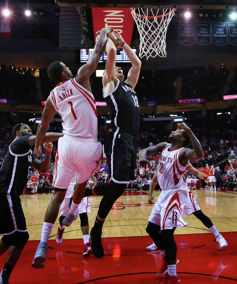 Rockets forward Trevor Ariza (7) rises to the occasion to block a shot by Nets forward Joe Harris on a crucial possession in the final minute Monday night. Photo: Mark Mulligan, Staff / © 2016 Houston Chronicle
