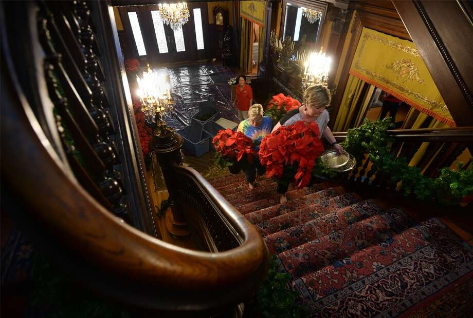 Becky Fertitta, left, and Karen Chapman haul poinsettias up the main staircase at the McFaddin-Ward House on Monday. Judy Linsley is also pictured. Several staff members worked Monday to decorate the home for the holidays. The museum will host its Christmas Photo Opportunity on December 4 and and Eggnog Open House on December 15.   Photo taken Monday, November 28, 2018 Guiseppe Barranco/The Enterprise Photo: Guiseppe Barranco/The Enterprise