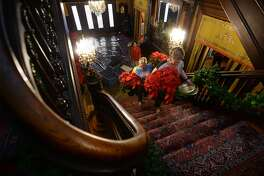 Becky Fertitta, left, and Karen Chapman haul poinsettias up the main staircase at the McFaddin-Ward House on Monday. Judy Linsley is also pictured. Several staff members worked Monday to decorate the home for the holidays. The museum will host its Christmas Photo Opportunity on December 4 and and Eggnog Open House on December 15.   Photo taken Monday, November 28, 2018 Guiseppe Barranco/The Enterprise