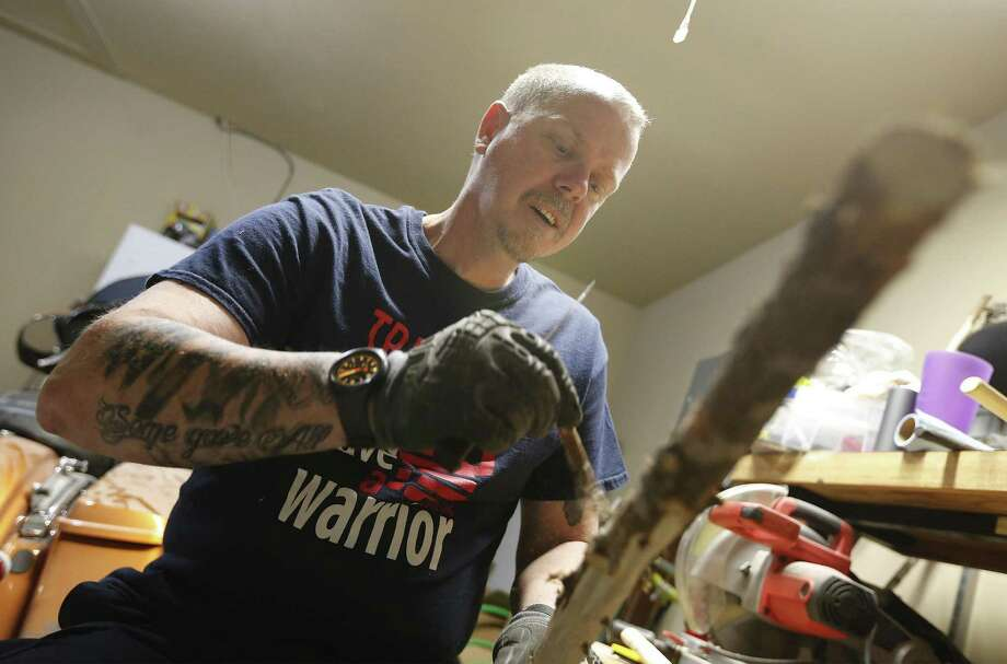 Army veteran Greg Huston of Seguin peels away tree bark since he has learned to make walking sticks by hand and gives them away for free to fellow veterans. He said he learned the hobby during his deployments overseas. On afternoons in his garage, Huston can be found whittling. He takes limbs of pecan and cedar and crafts them into walking sticks and canes for veterans. Huston says carving the walking sticks is a form of therapy for his service-connected PTS. (Kin Man Hui/San Antonio Express-News) Photo: Kin Man Hui, Staff / San Antonio Express-News / ©2016 San Antonio Express-News