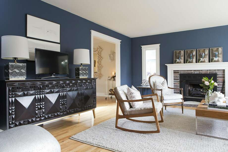 The living room of Nadine Curtis and Ben Wells is painted Benjamin Moore Moby Dick blue, a reference to Curtis' East Coast roots. The pillows and chairs are upholstered in fabric from Africa; Curtis lived in South Africa for two years. Photo: Vivian Johnson, Special To The Chronicle