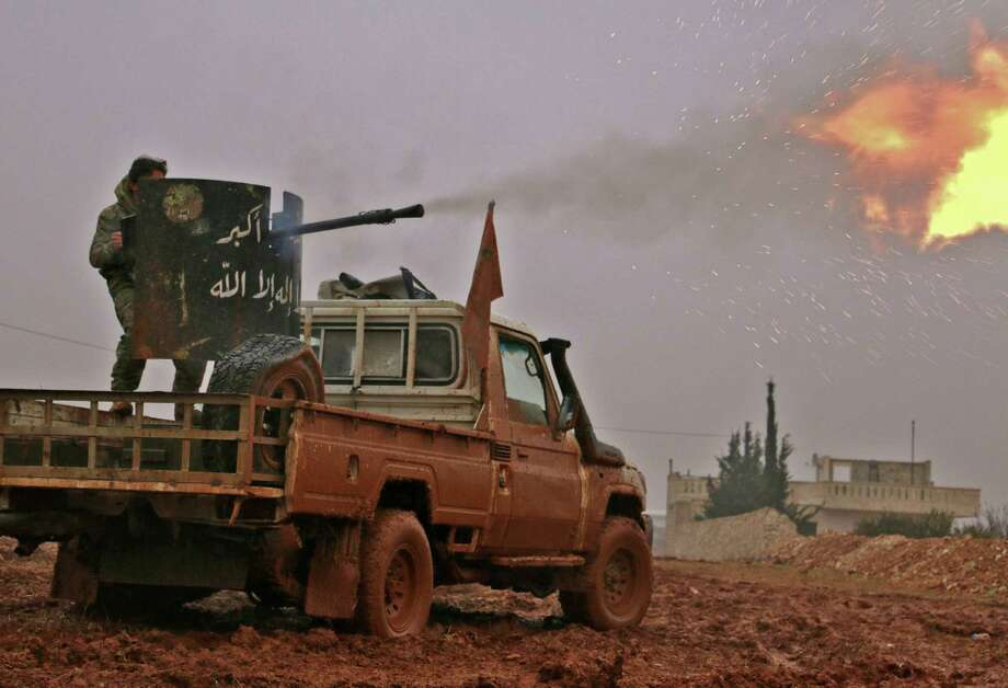 TOPSHOT - Syrian opposition fighters fire towards positions held by Islamic State (IS) group jihadists in al-Bab on the northeastern outskirts of the northern embattled city of Aleppo on December 13, 2016.  / AFP PHOTO / Saleh ABO GHALOUNSALEH ABO GHALOUN/AFP/Getty Images Photo: SALEH ABO GHALOUN, Stringer / AFP/Getty Images / AFP or licensors