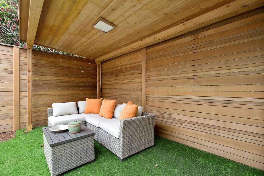 A covered patio sits beside the hot tub in the backyard and creates a perfect seating area.  Photo: Open Homes Photography