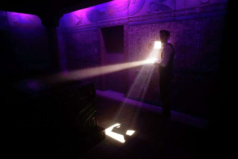 Zephyr Goza, operations manager for Five Wits reflects a beam of light to illuminate an area inside the burial chamber in the Tomb to complete a task during a media tour of Five Wits at Crossgates Mall on Tuesday, Dec. 13, 2016, in Guilderland, N.Y. Five Wits is an interactive adventure game where participants solve problems and figure out how to work together as they make their way through various rooms. (Paul Buckowski / Times Union)