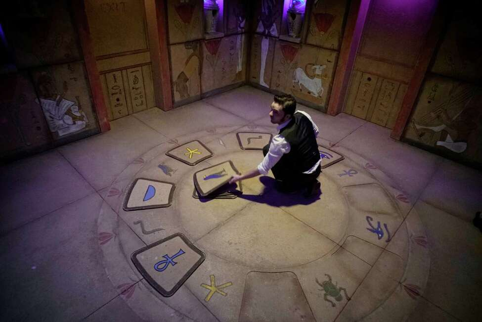 Zephyr Goza, operations manager for Five Wits, figures out a puzzle on the floor in one of the rooms inside the Tomb during a media tour of Five Wits at Crossgates Mall on Tuesday, Dec. 13, 2016, in Guilderland, N.Y. Five Wits is an interactive adventure game where participants solve problems and figure out how to work together as they make their way through various rooms. (Paul Buckowski / Times Union)