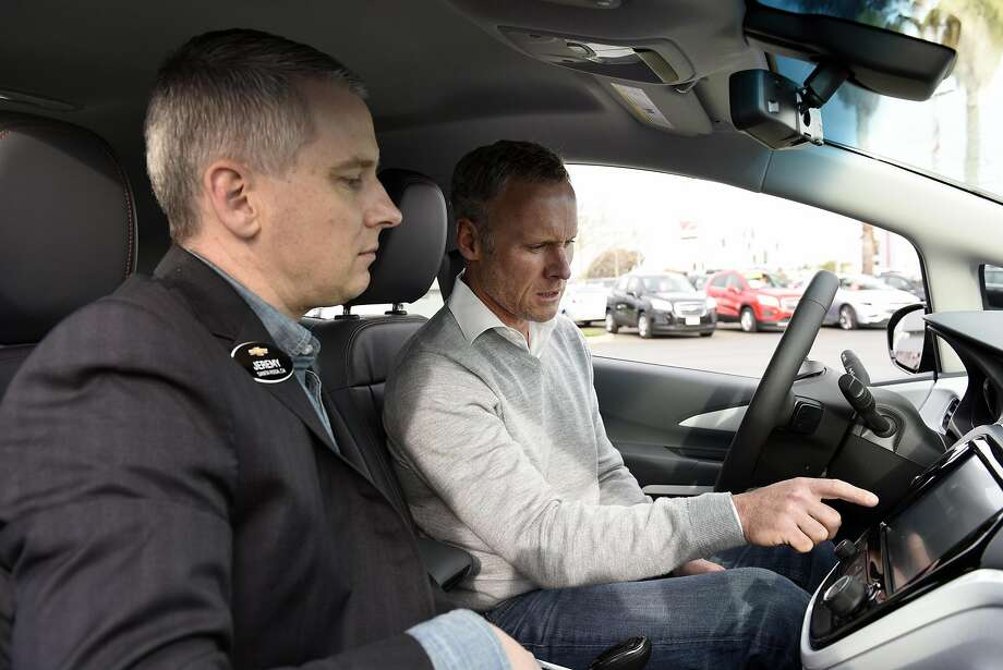 Steve Henry (right) of Portola Valley gets some operating instructions on his new Bolt from Chevrolet district manager Jeremy Sanford. Photo: Michael Short, Special To The Chronicle