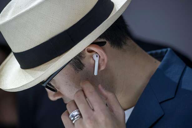 An attendee wears the Apple Inc. AirPod wireless headphones during an event in San Francisco, California, U.S., on Wednesday, Sept. 7, 2016. Apple Inc. unveiled new iPhone models Wednesday, featuring a water-resistant design, upgraded camera system and faster processor, betting that after six annual iterations it can still make improvements enticing enough to lure buyers to their next upgrade. Photographer: David Paul Morris/Bloomberg