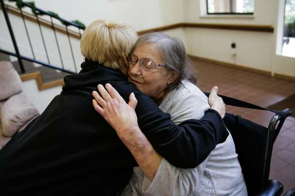 Sandra Quiroz (right), a senior who was recently evicted from a mobile home park when it was sold to a developer, gets a hug from her neighbor Irma Ward (left) at her senior apartment complex, in Benicia, Calif., on Sunday, Dec. 11, 2016. Quiroz, who is on oxygen and dialysis, was in danger of becoming homeless until the Benicia Community Action Council stepped in and found her a new place to live in an affordable senior housing residence.
