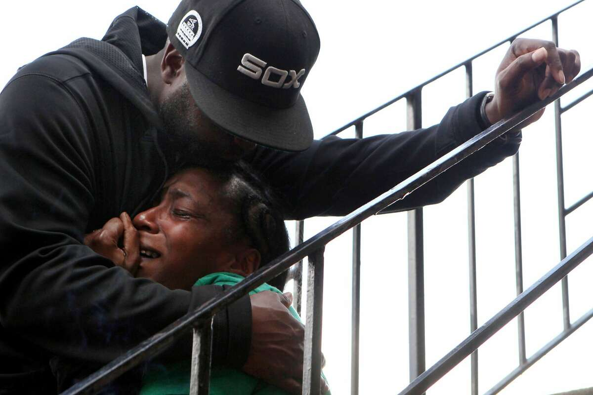 Marquita Brown is comforted by Michael Walker, Monday, March 2, 2015, in Oakland, Calif. Police say Brown's son Davon Ellis was walking with his friends last Saturday when he was shot on the 3300 block of Brookdale Avenue, east of Coolidge Avenue. Police and paramedics performed CPR on Davon, but he died at a hospital.