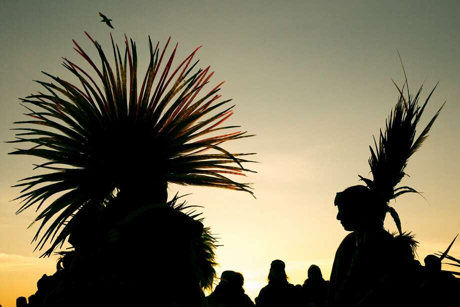 During sunrise, Veronica Hernandez (right) and the Eztli Chicahua group dance during the Indigenous People's Sunrise Gathering at Alcatraz Island, on Thursday, Nov. 24, 2016 in San Francisco, Calif. The gathering has been an annual tradition since 1975. Also known as Unthanksgiving Day, the event commemorates the 1969-71 occupation of Alcatraz by American Indians. Photo: Santiago Mejia, The Chronicle
