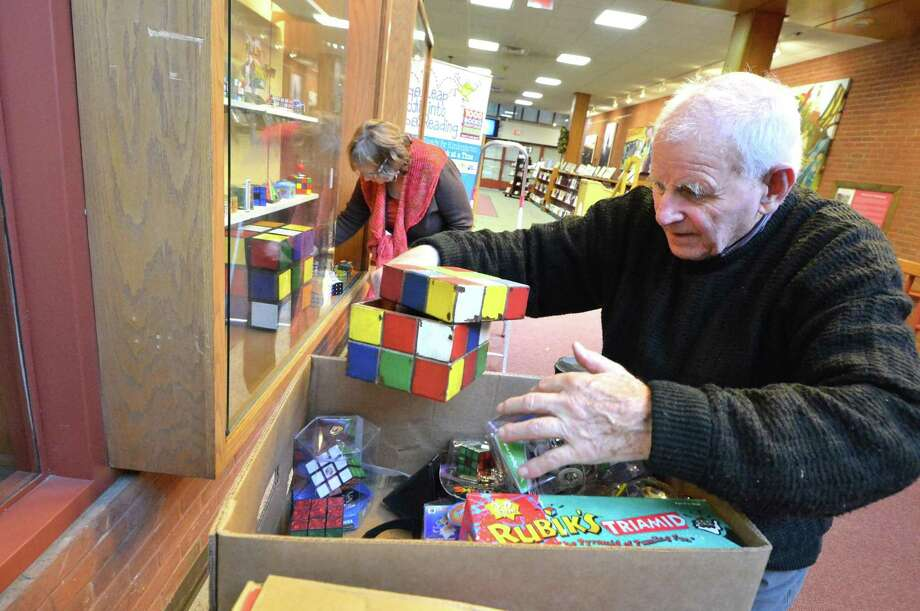Andre Farkas grabs some Rubik's Cubes from his collection on Wednesday December 7, 2016, that will be displayed at the Norwalk Public Library throughout the month of December. Norwalk resident Andre Farkas Started collecting them and all things related to the cube more than 20 years ago when he got one as a gift. The collection will be in the Norwalk Conn. Main Library display Photo: Alex Von Kleydorff / Hearst Connecticut Media / Connecticut Post
