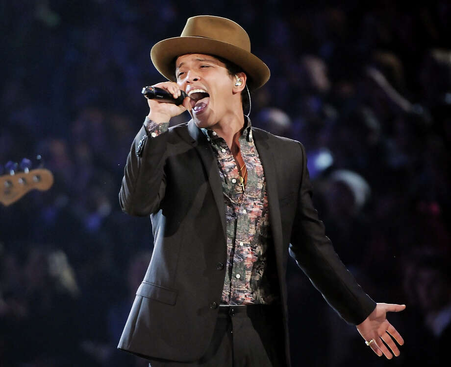In this Nov. 7, 2012 file photo, Bruno Mars performs during the 2012 Victoria's Secret Fashion Show in New York. Las Vegas is set to ring in 2014 with big-name concerts, celebrity-hosted parties and an eight-minute rooftop fireworks display billed as the nation's largest. Mars is christening the Cosmopolitan's new Chelsea Ballroom. The show will be broadcast live on the casino's 65-foot (20-meter) marquee to ice skaters at a rooftop rink and partyers on the Strip below. (Photo by Evan Agostini/Invision/AP) Photo: Evan Agostini, INVL / Invision