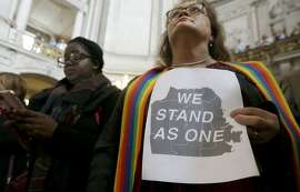 The Rev. Annie Steinberg-Behrman, right, provisional pastor with Metropolitan Community Church, holds a sign while listening to speakers at a meeting at City Hall in San Francisco by city leaders and community activists to reaffirm the city's commitment to being a sanctuary city in response to Donald Trump's support of deportations and other measures against immigrants Monday, Nov. 14, 2016. (AP Photo/Jeff Chiu)